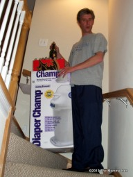 Oooohhhhh, the Diaper Champ. Better than the Diaper Genie because it used regular garbage bags. No better than any similar product because they all reek after a couple days worth of diapers. But notice the bottle of wine mysteriously coming out of the top of the box.
